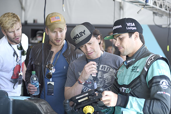 LONG BEACH, CA - APRIL 2:   Actors Glen Powell, Austin Stillwell, and Clifton Collins Jr. get some one-on-one time in the garage with the 2015 champion, Nelson Piquet Jr. (BRA).